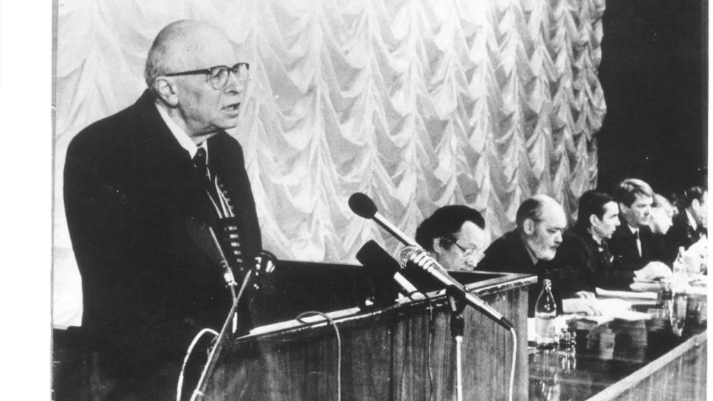 (Sakharov à la tribune de la conférence constitutive de « Memorial », le 28 janvier 1989. A droite : A. Adamovitch, Iou. Kariakine, L. Ponomariov, Iou. Afanassiev, E. Jemkova, E. Evtouchenko, membres du bureau de l'association)